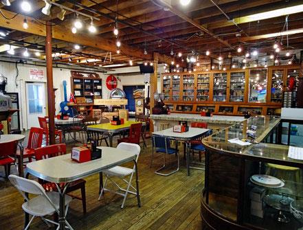 Motoglobe_Motorradreisen. Das Innern des Geschäftes ist voll mit Tischen und Stühlen und alten Regalen mit Produkten.