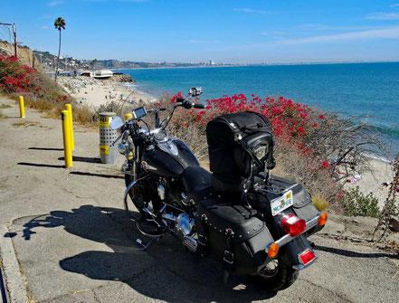 Motoglobe Motorradreisen. Die Harley steht am Strassenrand mit Blick auf das blaue Meer und Häuser von Santa Monica, Kalifornien, USA,  im Hintergrund.