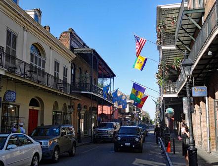Motoglobe._Motorradreisen. In einer Nebenstrasse des French Quarters in New Orleans stehen und fahren viele Autos und auf den Gehsteigen hat es viele Leute.