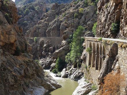 Motorradreisen, ein Fluss mit Brücke mit vielen Felsen in einer Schlucht