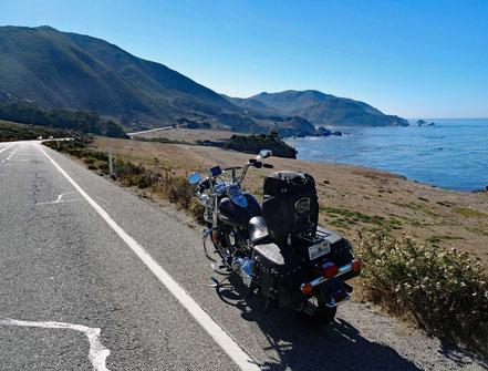 Motoglobe Motorradreisen. Die Harley steht am Strassenrand des Highway Nr. 1 kurz im Hintergrund ist das Meer und die Berge zu sehen.