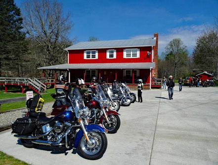 Motoglobe_Motorradreisen. Die Harley Davidson Motorräder stehen auf dem grossen Parkplatz vor dem Gebäude der Unterkunft Two Wheels of Suches.