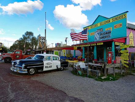 Motoglobe Motorradreisen. In der Ortschaft Seligman steht ein altes Polizeiauto am Strassenrand neben einem Holzhaus, in welchem ein Souvenirshop ist.