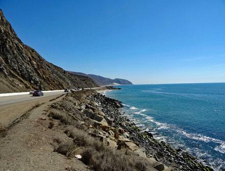 Motoglobe Motorradreisen. Die Strasse führt zwischen den Bergen und dem Meer entlang.
