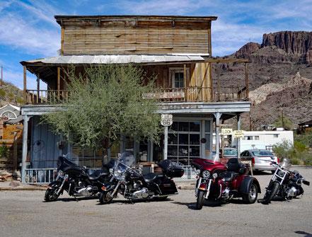 Motoglobe Motorradreisen. Vier Harley Davidson stehen vor einem alten Saloon in der Ortschaft Oatman.