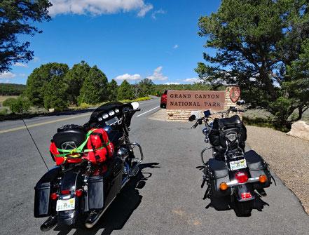 Motoglobe Motorradreisen. Die beiden Harley's stehen vor dem Hinweisschild zum East Rim Eingang des Grand Canyon National Park, Arizona, USA