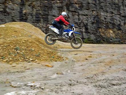 Motoglobe_Motorradreisen. Ein Motorradfahrer spring mit seiner Enduromaschine über einen kleine Hügel im Gelände.