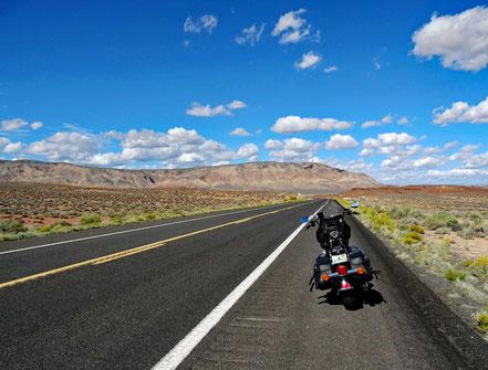 Motoglobe Motorradreisen. Die Harley steht am Strassenrand der State Route Nr. 64 und im Vordergrund sind Berge zu sehen.