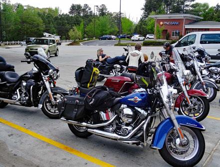 Motoglobe_Motorradreisen. Die Motorräder stehen auf eine grossen Parkplatz und jemand liegt auf der Harley Davidson und ist am entspannen.