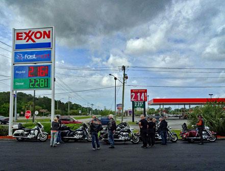 Motoglobe_Motorradreisen. Die Motorräder stehen zwischen zwei grossen Tankstellen auf einem Teerplatz und die Fahrer stehen dazwischen und reden miteinander.