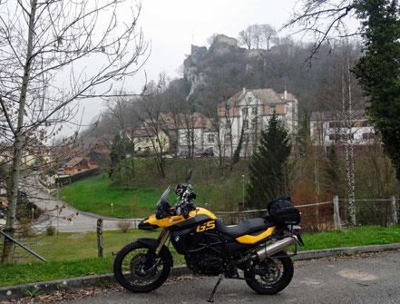 Motorradreisen: Die BMW f800 GS steht auf einem Parkplatz und im Hintergrund sieht man die Burgruinen in der Ortschaft Ferrette