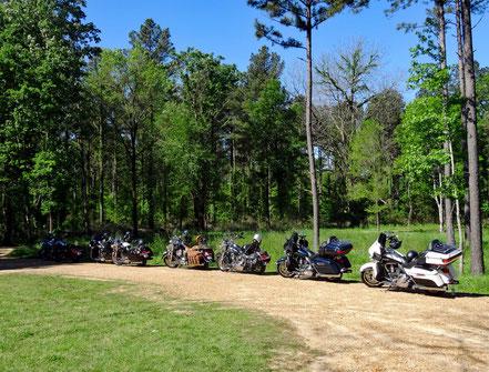 Motoglobe_Motorradreisen. Die Harely Davidsons stehen auf einem Kiesparkplatz vor der Windsor Ruinen umgeben von Wald und Wiesen