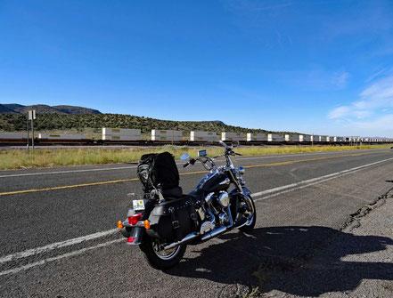 Motoglobe Motorradreisen. Die Harley steht am Strassenrand der Route 66 und neben der Strasse fährt einer der kilometerlangen Güterzüge vorbei.