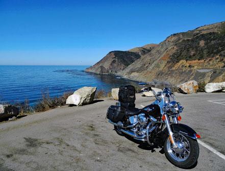 Motoglobe Motorradreisen. Die Harely steht auf einem Parkplatz und im Hintergrund befindet sich das Meer und die Berge.