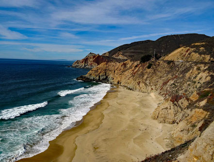 Motoglobe Motorradreisen. Wir blick auf eine schöne Bucht mit Sandstrand und blauen Meer umringt von braunen Felsen.