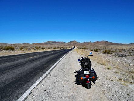Motoglobe Motorradreisen. Die Harley steht am Strassenrand der State Rd Nr. 190 und wir fahren durch karges Gebiet zum Death Valley Natl. Park. Nevada, USA
