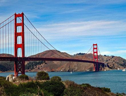 Motoglobe Motorradreisen. Die Golden Gate Brindge leuchtet rot und im Hintergrund sind Hügel und Häuser zu sehen.