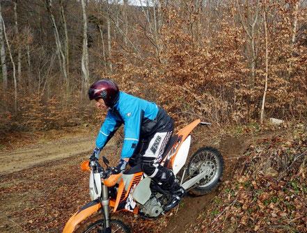 Motorradreisen. Eine Enduromaschien fährt eine Hügel im Gelände herunter an einem Sliding Kurs 2 der Cornu Masterschool