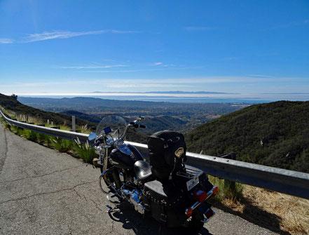 Motoglobe Motorradreisen. Die Harley steht an der San Marco Passstrasse und man sieht in der Ferne die Ortschaft Santa Barbara, das Meer, Hügel und Wälder.