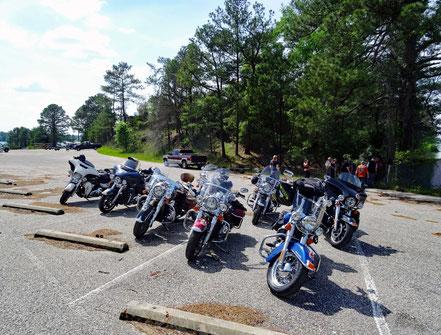 Motoglobe_Motorradreisen. Die Motorräder stehen auf einem grossen Parkplatz und die Fahrer und Fahrerinnen stehen dahinter herum.