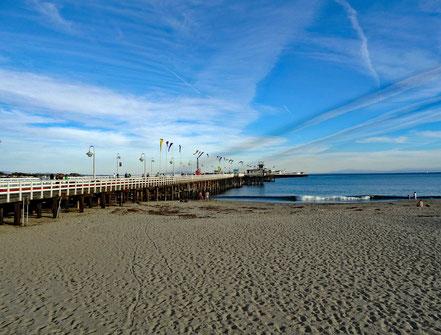 Motoglobe Motorradeisen. Der schöne braune Sandstrand und der lange Pier von Santa Cruz, Kalifornien, USA