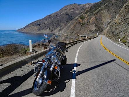 Motoglobe Motorradreisen. Die Harley steht am Strassenrand des Highway Nr. 1 und im Hintergrund sind die Berge des Big Sure Nationalparks zu sehen plus das Meer.