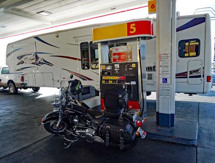 Motoglobe Motorradreisen. Die Harley steht an der Tanksäule und gegenüber steht ein riesiger Wohnwagen.