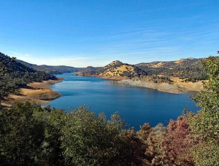 Motoglobe Motorradreisen. Es ist der schöne blaue Stausee des Flusses Tuolumne Rivers, Kalifornien, USA, zu sehen, welche eingebedet zwischen braunen Bergen liegt.
