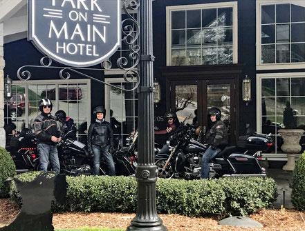 Motoglobe_Motorradreisen. Die Harley Davidson Motorräder stehen vor dem Haupteingang des aus Holz gebauten Hotels Park on Main in Highlands, North Carolina, USA