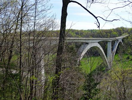 Motoglobe_Motorradreisen. Eine grosse weisse Brücke mit zwei Bögen führt über ein grünes Tal auf dem Natchez Trace Parkway Richtung Nashville.