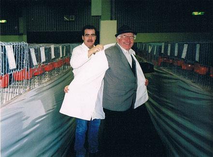 Ehemaliger Sonderrichter für Nürnberger und Fränkische Farbentauben und Ehrenmitglied Harry Cramer zieht auf der Schau des Jahres 2000 in Nürnberg den Preisrichterkittel mit Hilfe von Holger Kaps aus, er beendete damit seine Preisrichtertätigkeit.