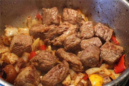 Das angebratene Rindfleisch kommt nun ebenfalls zu den Gewürzen hinzu