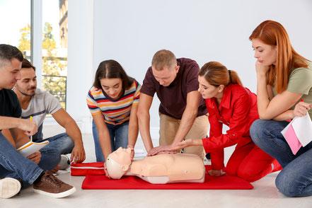 Gruppe von Menschen macht den Erste Hilfe Kurs