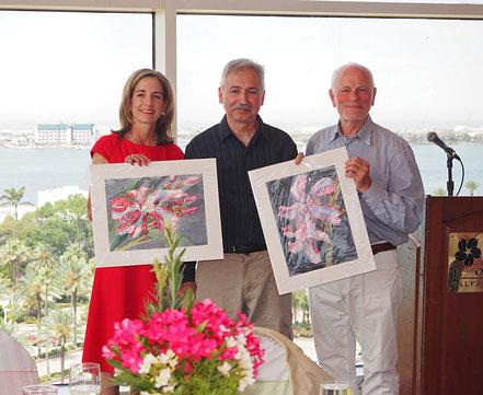 """Kimberly Gaido und James Nicholas nehmen von Willi Hufnagl von OLEANDER HAUS für die Oleander Society die Aquarelle """"Kewpie"""" entgegen."""