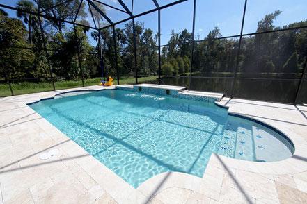 überdachter Pool mit hellen Natursteinfliesen und Bäumen im Hintergrund