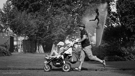 Vater mit Kinderwagen im Park. Statue im Hintergrund und Wassersprenger