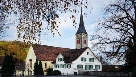 Kirche mit Kirchturm mit herbstlichen Ästen umrahmt