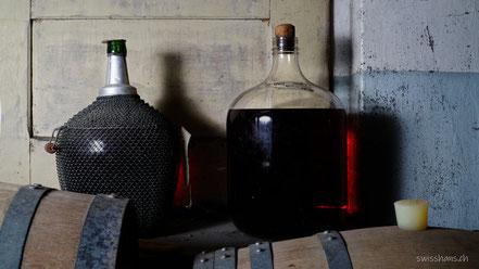 Whiskyfässer und Whiskyflaschen im Keller
