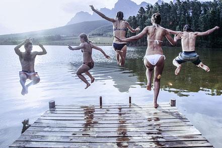 Familie springt ins Wasser im Urlaub - geschützt durch metavirulent