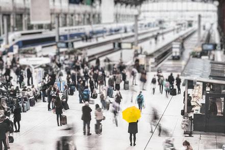 Geschützt durch metavirulent - Frau mit Regenschirm in Menschenmenge am Bahnhof