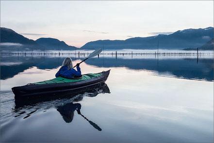 Frau mit Paddelboot auf See