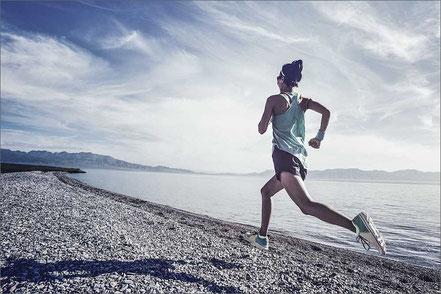 Frau läuft sportlich am Strand