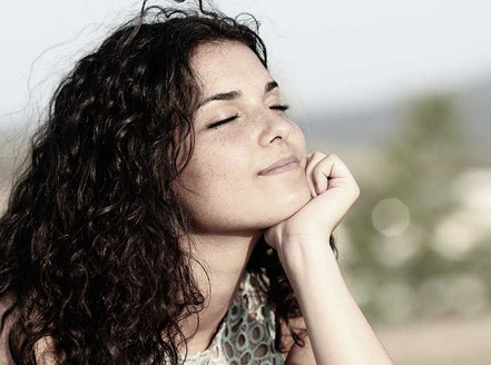 Frau hält entspannt das Gesicht in die Sonne