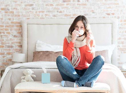 Frau erkältet mit Taschentuch und Schal auf dem Bett sitzend