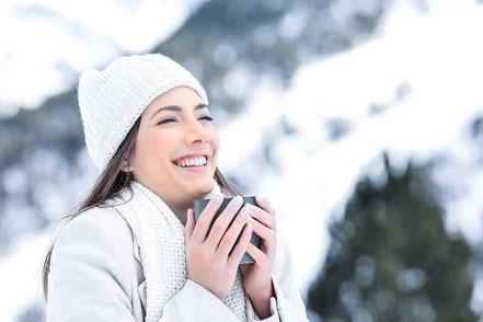 Frau im Urlaub in den Bergen bei Schnee mit warmer Tasse