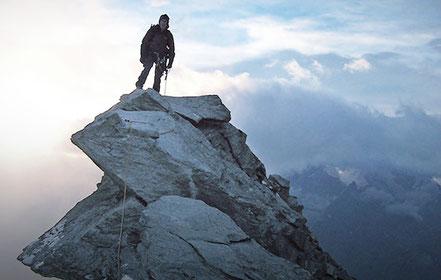 Bergsteiger steht auf dem Gipfel