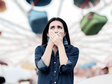 Frau hat Angst, hält sich die Hände vor den Mund und guckt entsetzt
