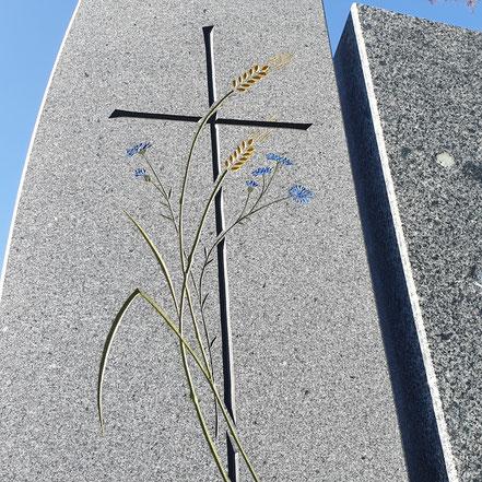 Farbig getöntes Kornblumen-Ornament auf einem Grabstein