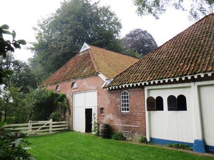 De achterzijde van de 19de-eeuwse landbouwschuur (links) en het koetshuis uit 1796 met de dubbele wagenpoort.