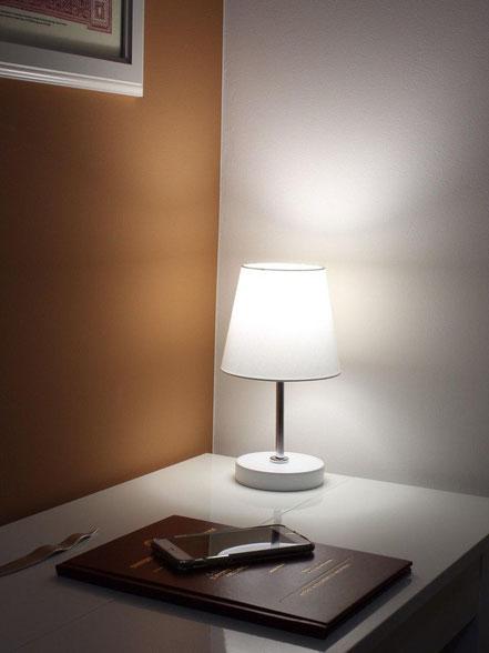 Lampada moderna su comodino della camera da letto.